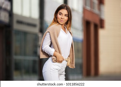 Young fashion woman walking in city street. Stylish female model wearing white shirt and ripped jeans