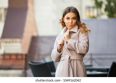 Young fashion woman walking in city street Stylish female model in light grey coat outdoors