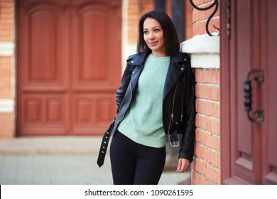 Young fashion woman walking in city street Stylish female model wearing black leather jacket and light green pullover