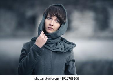 Junge Modefrau im Freien Stilvolles weibliches Modell in grauem klassischem Mantel und Kopfschal