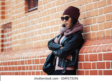 Young fashion woman wearing sunglasses scarf and beanie leaning on brick wall Stylish female model in black leather jacket outdoor