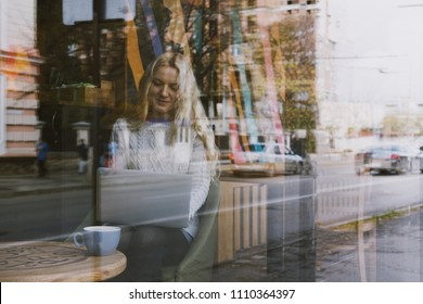Young fashion woman working on her laptop and sitting at the table and drinking coffee in cafe. Stylish female model with blonde hairs