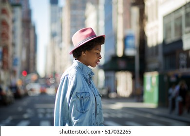 Young fashionable African American woman crossing the street, photographed in NYC in September.