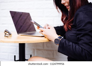 Young fashionable Asian business woman using a mobile phone and laptop over white brick background