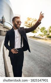 Young fashionable bearded Indian Arabic wearing sunglasses businessman calling for e-hailing taxi on city streets.