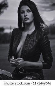 Young fashionable beautiful sexy brunette woman wearing leather jacket and ripped jeans posing outdoors. Attractive female with sensual decollete, black and white, toned image. 20 25 years old