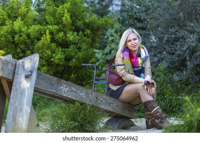 Young fashionable blonde woman sitting in a Park on an old wooden swing.