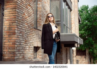Young fashionable business woman. Stylish female model in a white blouse and blue jeans. Sunglasses. Black jacket is standing near the office building.