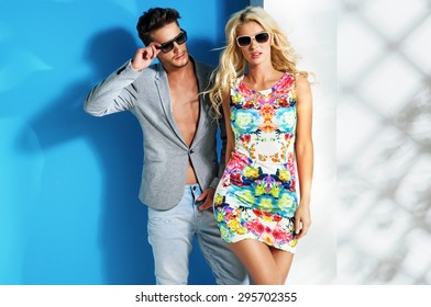 Young fashionable couple on cyan background