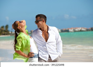 Young fashionable couple relaxing on the beach. Happy tourists is spending leisure time during vacation.