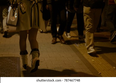 Young and fashionable female legs in high heels shoes walking on a busy street in Shinjuku, Tokyo, Japan.