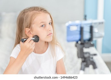 Young fashionable girl filming the video for her followers about makeup. Kids blogger concept