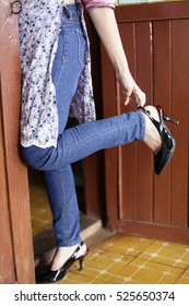 Young fashionable girl with long legs wearing black shoes on platform. Stand by the red door.