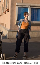 A young fashionable girl in an orange topic, a denim shirt and wide trousers stands near the house at sunset