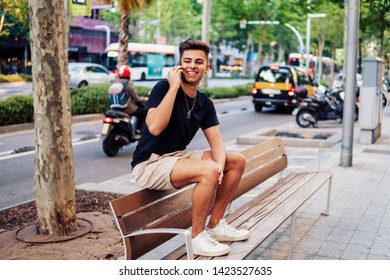 Young fashionable handsome man on the street of modern city talking on a cell phone. Communication concept