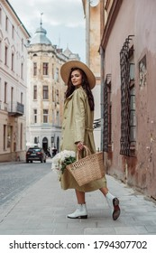 Young fashionable happy smiling woman wearing straw hat, long trench coat, holding wicker bag with flowers, walking in street of European city. Lifestyle, travel conception. Full body outdoor portrait