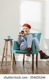 young fashionable lady sitting in an empty room with wooden floor and using her smartphone