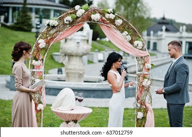 Young fashionable lovely couple with speech master of wedding ceremony against decor arch on wedding anniversary and marriage proposal.