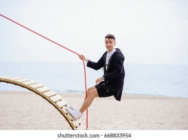 The young fashionable man climbs to the top on the stairs and rope climber, effort and reaching the goal with humor.