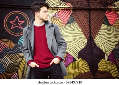 Young fashionable man standing in front of colorful wall. Autumn time outdoors.