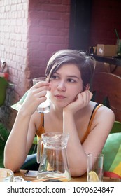 the Young fashionable pensive girl in an orange topic sits at a table in a cafe