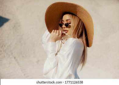 A young fashionable stylish  girl in a white dress  in the desert and loves the wind in a hot summer day, sunny weather wearing sunglasses and hat, playing with pearls jewerly