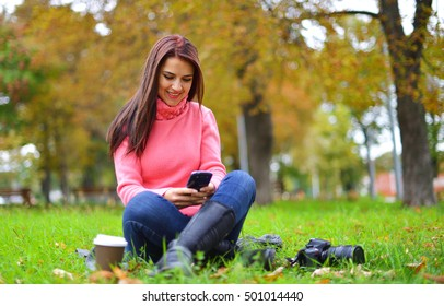Young fashionable teenage girl with smartphone, camera and takeaway coffee in park in autumn sitting at smiling.