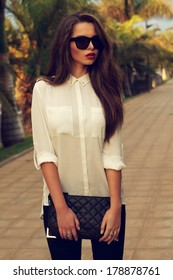 Young fashionable trendy girl posing at tropical alley between palms in evening soft light. Vogue style toned portrait of young woman in black jeans, white blouse and sunglasses holding handbag