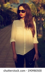 Young fashionable trendy girl posing at tropical alley between palms in evening soft light.  toned portrait of young woman in black jeans, white blouse and sunglasses holding handbag