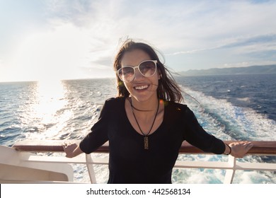 Young fashionable woman in black dress standing on shipboard enjoying sun on her face.Summer vacation,open sea, cruise. Luxury lifestyle,successful woman on earned cruise.Europe summer holidays.