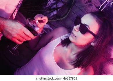 Young fashionable woman with cigarette using glass as ashtray.