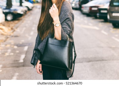 young fashionable woman holding her bag. wearing golden jewelry, and white watch. close up fashion details,