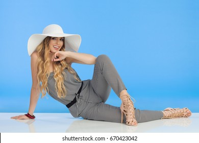 Young fashionable woman in jumpsuit, high heels and white sun hat is sitting relaxed on floor, holding hand on chin and looking at camera. Full length studio shot.