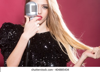 Young fashionable woman with pretty face holding retro microphone