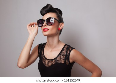 Young fashionable woman in round sunglasses posing in guipure dress. Red lips. Updo, twisted high bun. top knot