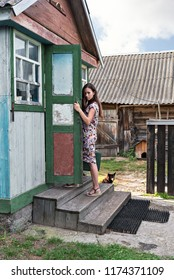 a young fashionable woman in a vintage retro dress rises the steps of a village shabby house with sheds holding the handle of a colorful door
