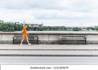 Young fashionable woman walking on the Queen Louise Bridge over Peblinge So. Traditional danish architecture of Copenhagen, Denmark