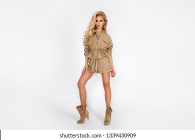 Young fashion,stylish smiling blond woman in the studio. Fashion trend apparel, safari style, summer outfit, white background, looking forward - Image