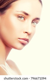 Young fasion model girl face. Natural lips, nude make-up, clean skin, green eyes. Facial and health treatment concept