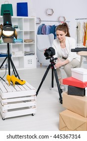 Young fasioner making photo of high-heeled shoes using the lamp and a tripod in her atelier