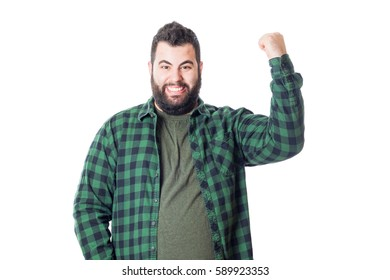 Young fat boy with green plaid shirt raising his fist isolated on white background