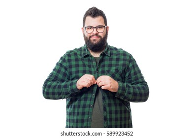 Young fat boy tying his green plaid shirt isolated on white background