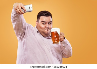 Young fat man at oktoberfest with beer on yellow background making selfie photo on smartphone.