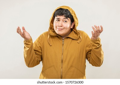 Young fat teenage girl with yellow sweatshirt with innocent face expression on gray background.