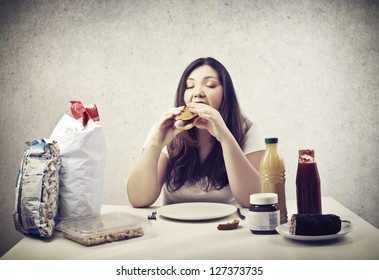 young fat woman eating hot dog sitting at the table