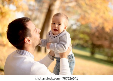 Young father and baby boy playing  in autumn park at sunny day