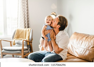 Young father with baby daughter on sofa at home