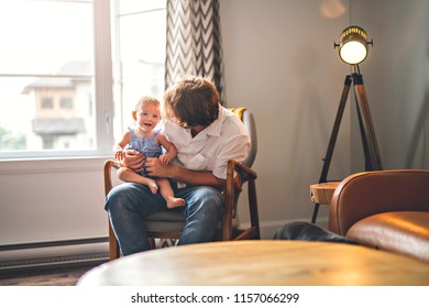 Young father with baby daughter on chair at home