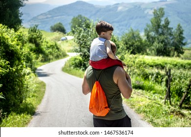 Young father with backpack, holding his son on shoulder going for walk. Back view of father carrying his son on shoulders. Family bonding in nature. Family time together.