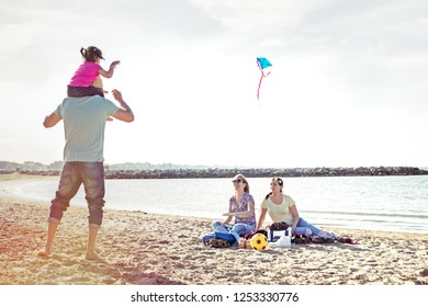 young father carrying cute little child on his shoulder while smiling mother and sister watching sitting on beach. family fun on beach playing with a kite. concept of family vacation and togetherness